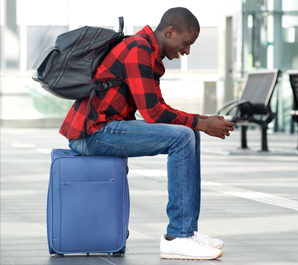 Young man sitting on suitcase at airport